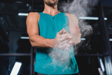Cropped view of sportsman with talcum powder in sports hall