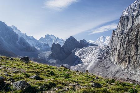 Bellissimo paesaggio con vegetazione verde e montagne rocciose innevate, Kirghizistan, Ala Archa Archivio Fotografico