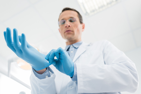 Doctor wearing medical gloves in modern  clinic