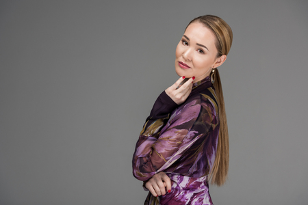 Beautiful Kazakh woman posing and looking at camera isolated on grey