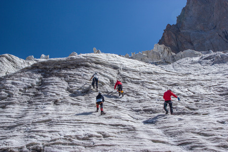 Back view of hikers climbing at beautiful snow capped mountains, Kyrgyzstan, Ala Archa Stock Photo