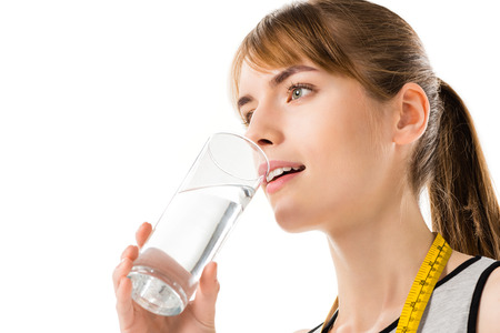 Young woman with measuring tape on neck drinking water isolated on white Stock Photo