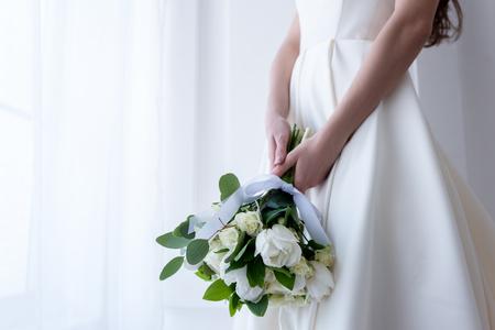 Vue recadrée de la mariée en costume traditionnel tenant le bouquet de mariage