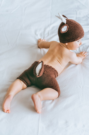 Beautiful infant child in knitted deer costume in bed