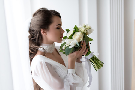 Attractive bride in wedding dress and veil sniffing white bouquet Imagens