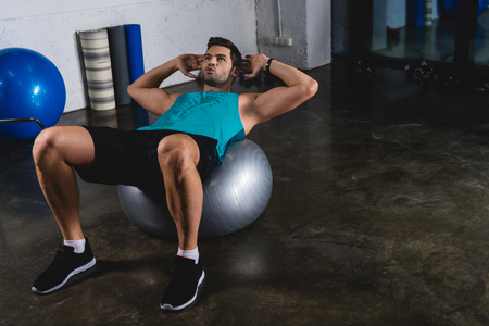 Sportsman doing abs on fit ball in sports hall