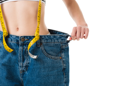 Cropped shot of slim woman with measuring tape in oversized jeans isolated on white