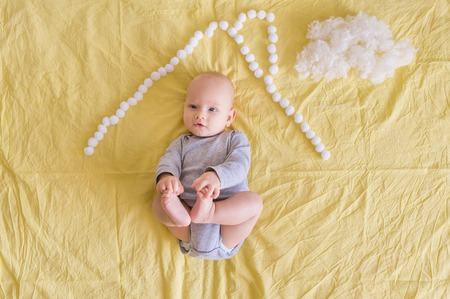 Top view of adorable child lying under house roof made of cotton balls and cotton cloud on bed Imagens