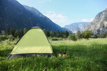 Tent with shoes on green grass in beautiful mountains, Altai, Russia