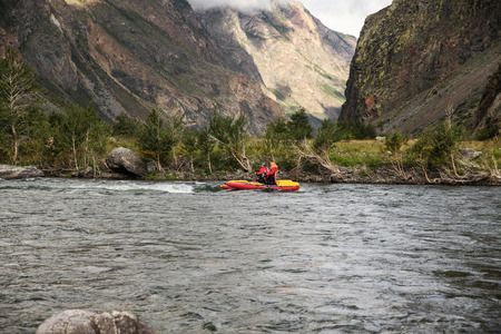 Side view of people on kayaks rafting on mountain river and beautiful landscape, Altai, Russia Stock Photo