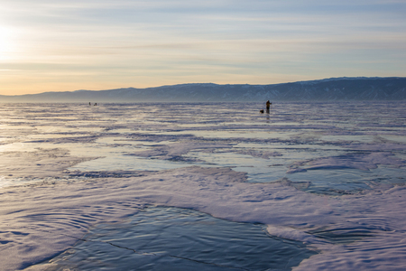Male hiker with backpack walking on ice water surface against hills on shore, Russia, lake Baikal