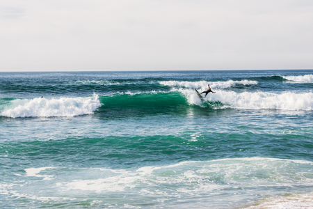 Unidentified surfer on surfboard riding wave and beautiful seascape at cloudy day, Portugal