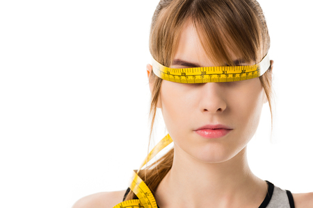 Close-up portrait of young woman with measuring tape tied around her eyes isolated on white