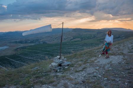 Woman walking in beautiful mountainous landscape with windsock waving in Crimea, Ukraine. Stock fotó