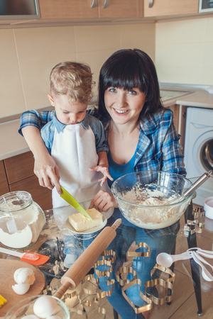 Smiling mother helping son cut butter with plastic knife Banco de Imagens