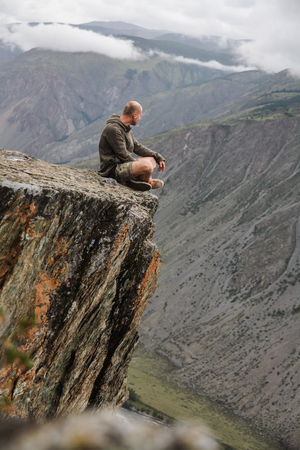 Young man sitting on cliff and looking beautiful landscape, Altai, Russia Reklamní fotografie