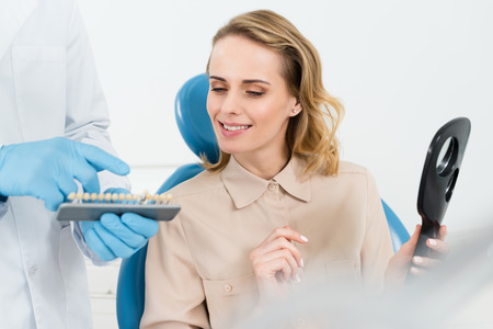Doctor showing tooth implants to female patient in modern dental clinic Foto de archivo