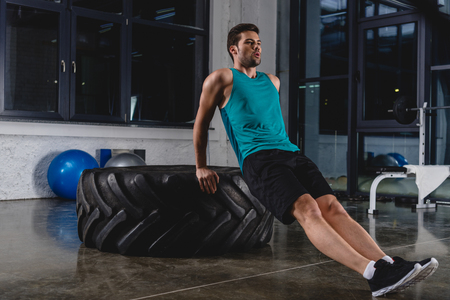 Sportsman doing push ups on tire in gym Stockfoto