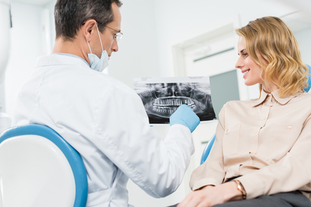 Woman consulting with dentist looking at x-ray in modern clinic