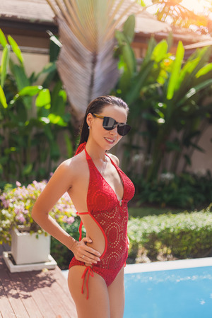 Smiling young woman in red knitted swimsuit at poolside 写真素材