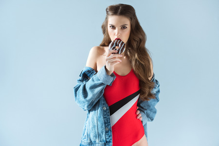Seductive girl in red swimsuit biting donut and looking at camera isolated on grey Stock Photo