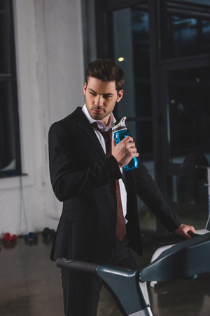 Manager in suit training on treadmill with sport bottle in gym Stok Fotoğraf