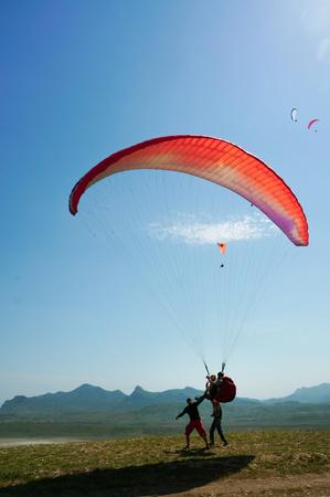 Two men parachuting on field with hills on backgrond, Crimea, Ukraine Zdjęcie Seryjne