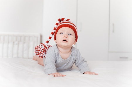 Portrait of adorable infant child in knitted hat lying on bed