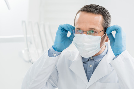 Doctor wearing medical mask in modern dental clinic Stock Photo
