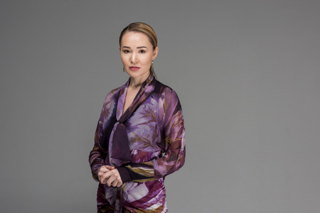 Portrait of beautiful fashionable Kazakh woman looking at camera isolated on grey Stok Fotoğraf - 112760810