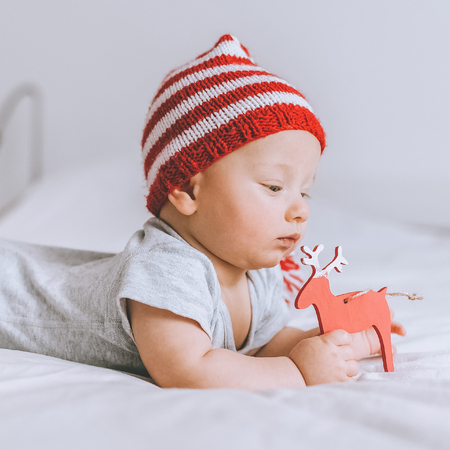 Close-up portrait of infant child in knitted striped hat playing with toy deer in bed