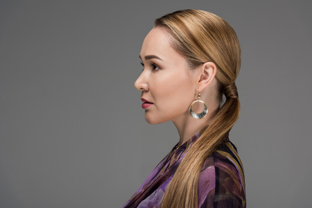 Profile portrait of beautiful Kazakh woman looking away isolated on grey