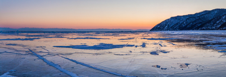 Beautiful scenic landscape with shore and frozen lake Baikal at sunset
