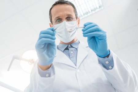 Dentist checking patient teeth with mirror in modern clinic