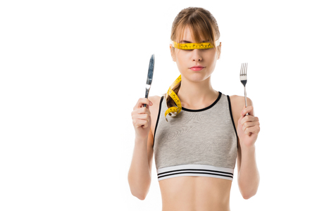 Slim woman with measuring tape tied around her eyes holding fork and knife isolated on white