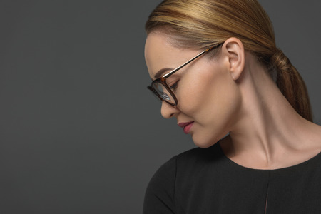 Profile of beautiful Kazakh woman in eyeglasses isolated on grey