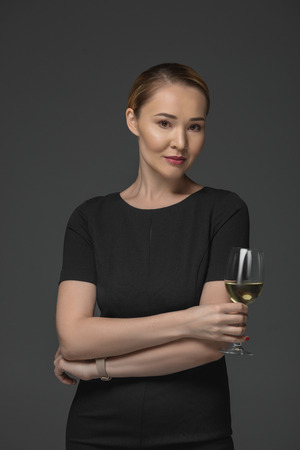 Beautiful Kazakh woman holding glass of wine and looking at camera isolated on grey Stok Fotoğraf