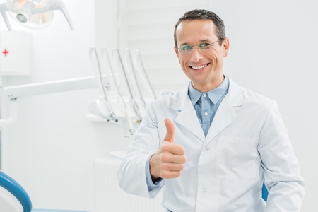 Dentist showing thumb up in modern dental clinic