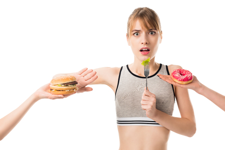 Young slim woman refusing of junk food and eating broccoli isolated on white