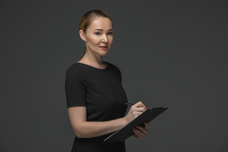 Smiling Kazakh businesswoman writing on clipboard and looking at camera isolated on grey