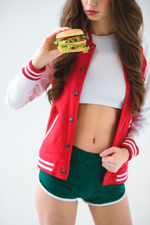 Cropped image of seductive girl in baseball jacket holding burger isolated on white