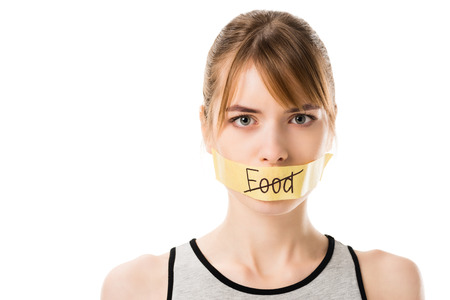 Woman with striked through word food covering mouth isolated on white