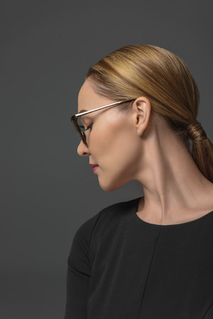 Profile of attractive Kazakh woman in spectacles isolated on grey Stok Fotoğraf
