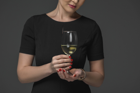 Cropped shot of woman in black dress holding glass of wine isolated on grey Stock Photo