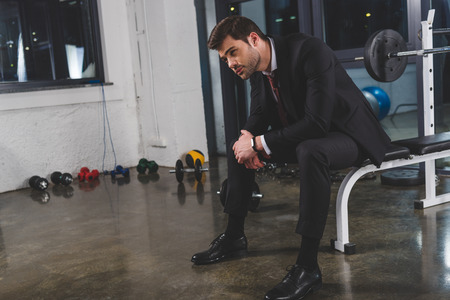 Tired businessman in suit with fitness tracker sitting in gym with dumbbells Stockfoto