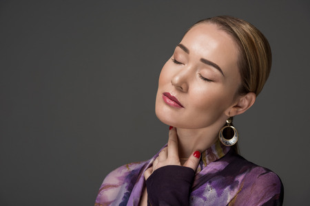 portrait of sensual kazakh woman with closed eyes posing isolated on grey Stock Photo
