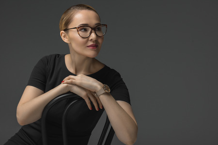 beautiful kazakh woman in eyeglasses sitting on chair and looking away isolated on grey