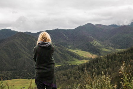 back view of young woman looking at beautiful landscape in mountains, Altai, Russia
