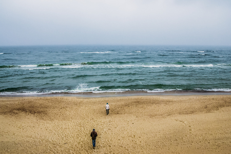 back view of couple walking on seashore and looking at wavy sea, Curonian Spit, Lithuania