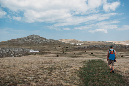 back view of hiker with backpack walking in mountains, Ukraine, Crimea, july 2012 Stock fotó